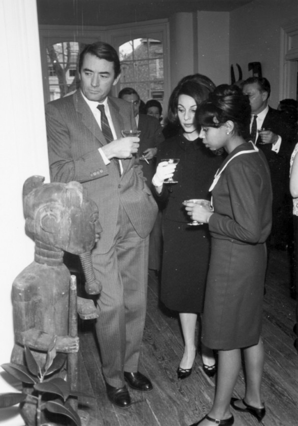 Actor Gregory Peck, Veronique Peck, and unidentified woman admire African art at Museum of African Art