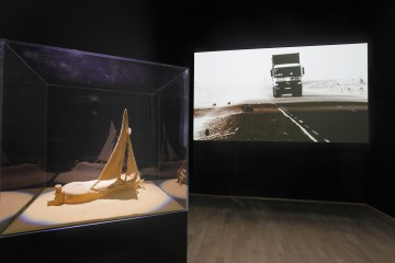 Zineb Sedira  b. 1963, France Guiding Light 2013 Single-screen projection HD video with sound (6 min. 15 sec.), model boat, sand  Installation: dimensions variable  Collection of the artist, courtesy Galerie Kamel Mennour, Paris