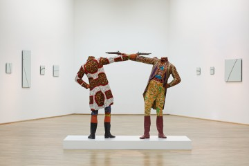 Yinka Shonibare MBE b. 1962, Great Britain How to Blow Up Two Heads at Once (Gentlemen) 2006 Mannequins, guns, Dutch wax printed cotton textile, leather riding boots, plinth 175 x 245 x 122 cm (68 7/8 x 96 1/2 x 48 in.) Sindika Dokolo Collection, Luanda